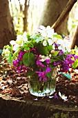 Sommerliches Blumensträusschen in violett und weiß mit grünen Blättchen in Trinkglas auf Baumstumpf im sonnigen Laubwald