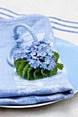 Napkin arrangement: forget-me-nots and lady's mantle leaf tied with blue cord on blue linen napkin