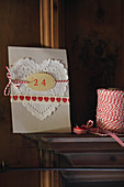 Hand-crafted Christmas card with heart-shaped paper doily