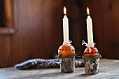 Hand-crafted Advent arrangement of candlesticks made from beakers and oranges stuck with cloves