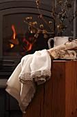 Weisses Leinentuch mit gehäkeltem Saum und Holzscheite auf Holzblock vor Kaminfeuer in Kanonenofen