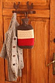 Cardigan and hot water bottle with felt and knit cover on coat pegs on wooden door