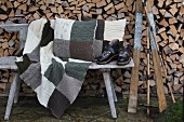 Vintage skiing equipment, knitted patchwork blanket and cushions on weathered wooden bench in front of stacked firewood