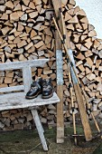 Vintage skiing equipment on weathered wooden bench in front of firewood stacked against house facade
