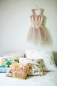 Scatter cushions with cheerful floral patterns on bed and tutu hanging on wall