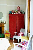 White chairs with colourful scatter cushions and red-painted cupboard in corner of child's bedroom