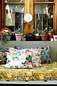 Floral cushions and mattress on couch in front of potted plants on window sill