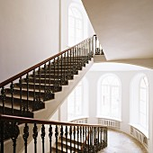 Grand stairwell - wrought iron balustrade on staircase and tall arched windows on landing