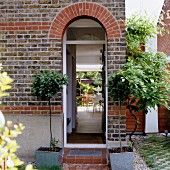 Arched doorway in brick facade of residential house and view of terrace seating area through open door