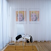 White shell chair in front of standard lamp next to transparent curtains; pair of portraits of Marilyn Monroe behind curtains