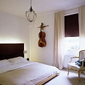 Modern bed with black, backlit headboard and cello decorating wall next to window with half-closed roller blind