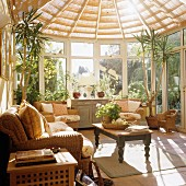 Light-flooded conservatory with wicker sofa set and traditional-style coffee table with turned wooden legs