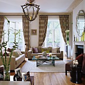 Classic sofa set and metal-framed coffee table on pale rug in front of French windows with beige, striped curtains