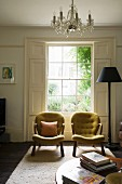 Two vintage armchairs in front of lattice window with interior shutters and standard lamp in traditional, elegant ambiance