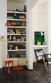 Red, metal standard lamp and red stool in front of fitted bookshelves next to open doorway and view of vintage armchair