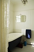 Vintage bathroom with white, wood-clad walls and lace curtain to one side
