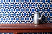 Old metal coffee pot on wooden table against tiled wall