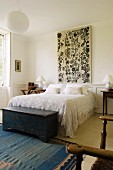 Bedroom with rustic wooden trunk at foot of double bed with lace bedspread and large wall panel with floral motif