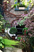 Potted plants in flowering garden adjoining house with brick facade