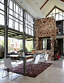 Wohnraum im Industriestil mit verglasten Fensterfronten & eingebautem Kamin in Trennwand aus Natursteinen