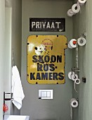 Guest toilet decorated with metal signs & multiple toilet roll holders