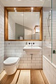 White-tiled bathroom with square mirror in niche and glass shower screen