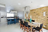 Rustic, solid wood dining table with elegant black chairs in front of brick wall below pendant lamp shaped like icicles