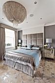 Fürstliches, silberfarbenes Doppelbett mit hohem, samtbezogenen Kopfende unter prunkvoller Deckenleuchte