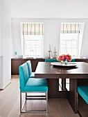 Brown, solid wood dining table with turquoise metal chairs; long sideboard below windows in background