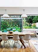 Classic chairs and modern wooden dining table in front of open terrace door with view of terrace and garden