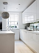 White kitchen counter with mirrored splashback and spherical lamp above island unit