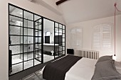 Minimalist bedroom in black, grey and white; glass partition offers view into bathroom with antique, free-standing bathtub