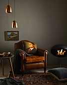 Winter shopping trends: leather armchair with scatter cushions, side table, Persian rug, floor cushion, stove, picture and pendant lamps