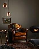 Shopping-Trends für den Winter: Polsterstuhl mit Lederbezug und Zierkissen, Beistelltisch, Perserteppich, Bodenkissen, Kaminofen, Wandbild und Hängelampen