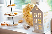 A house-shaped candle lantern, a popcorn wreath and a tiered cake stand of biscuits