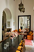Moroccan lantern lamps above long dining table and seating area with large mirror in background