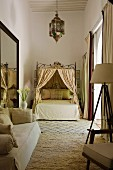 Moroccan bedroom in shades of cream with sofa, canopied bed and lantern-shaped ceiling lamp
