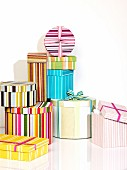 Stacked, striped, decorative boxes of various sizes, shapes and colours embellished with ribbons