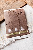 Card decorated with Christmas trees printed with hand-carved stamp, washi tape and dried flowers