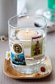 Candle lantern made from glass decorated with maritime postage stamps