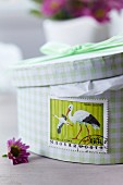 Stamp with stork motif stuck on gift box for baby shower
