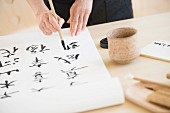 Woman painting Oriental characters on roll of paper using paintbrush