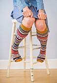 Woman wearing colourful knee socks & skirt sitting on stool