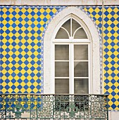 House facade with window, balcony & colourful wall tiles (Lisbon, Portugal)