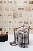 Blankets on armchair in front of numerous unframed etchings on wall