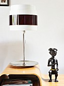 Retro table lamp with metal base next to ethnic stone figurine on moulded wood table