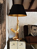 Table lamp with antler-shaped brass base on small drawer units next to armchair with photo-print cushion