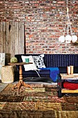 Rustic wooden side table on patchwork rug in front of dark blue sofa against rustic brick wall; pendant lamp with bundle of spherical lampshades
