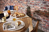 Baked goods on round oak table next to rustic brick wall