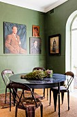 Retro metal chairs at round table in corner of green-painted room with paintings on wall